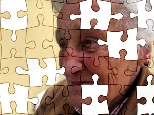 Alzheimer's & Dementia - Image of a jigsaw of an old woman's face with pieces of the puzzle missing