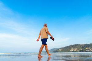 Anti-aging - Image of a Senior walking on the beach