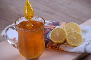 Bronchitis - Honey and lemon drink, cut lemons and honey dripping into liquid