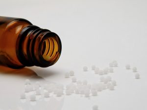 Image of homeopathic pills falling from a brown bottle