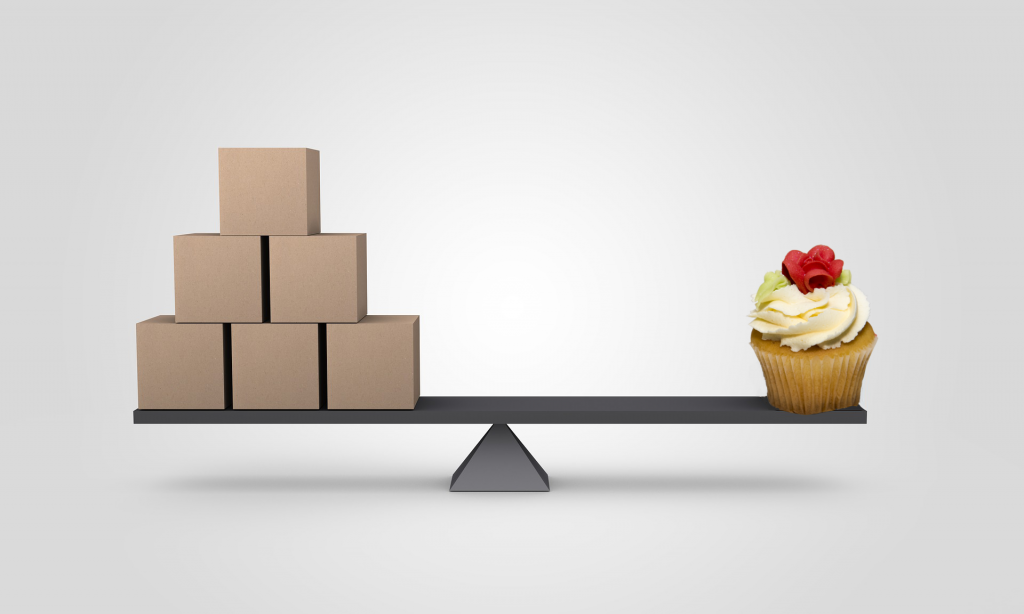 Photo of wooden blocks balanced against a cupcake on a wooden plank