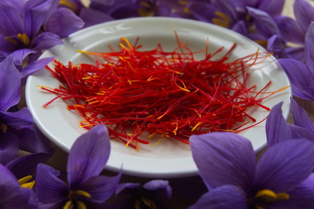 A bowl of red saffron spice among purple flowers