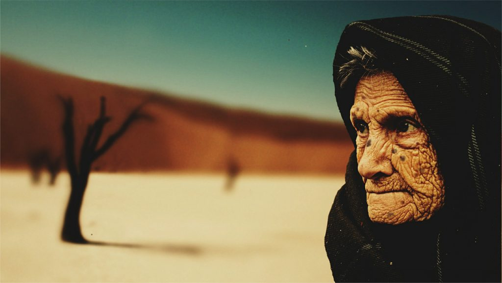 Image of an old, wrinkled woman in the desert