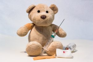 Image of a teddy bear with a hypodermic needle.