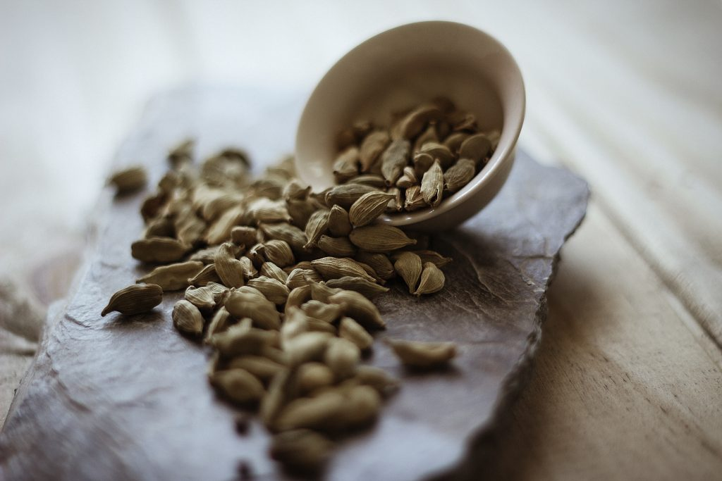 Image of cardamom pods spilling from a bowl