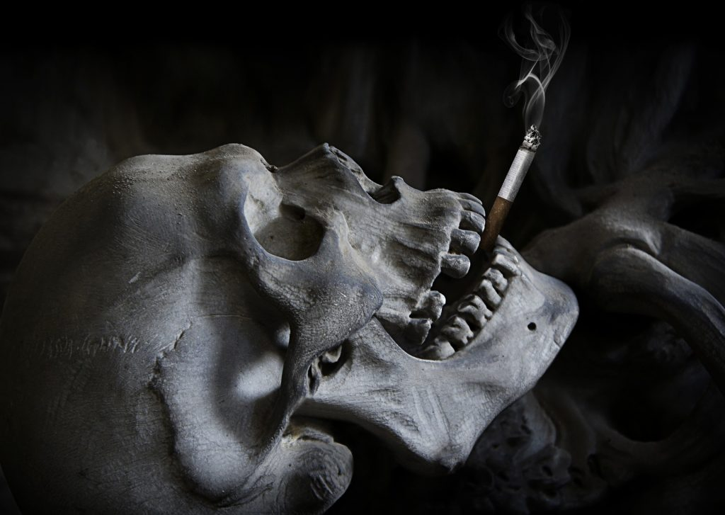 Image of a Skull with a smoking cigarette between its teeth - smoking kills