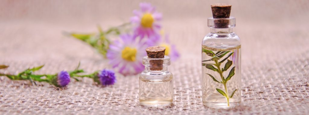 Cellulite - 2 bottles of essential oils and flowers on a table