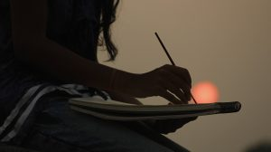 Stress management - Image of girl painting at sunset by the sea