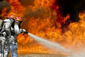 Image of firefighters spraying a fire with water from a fire hose