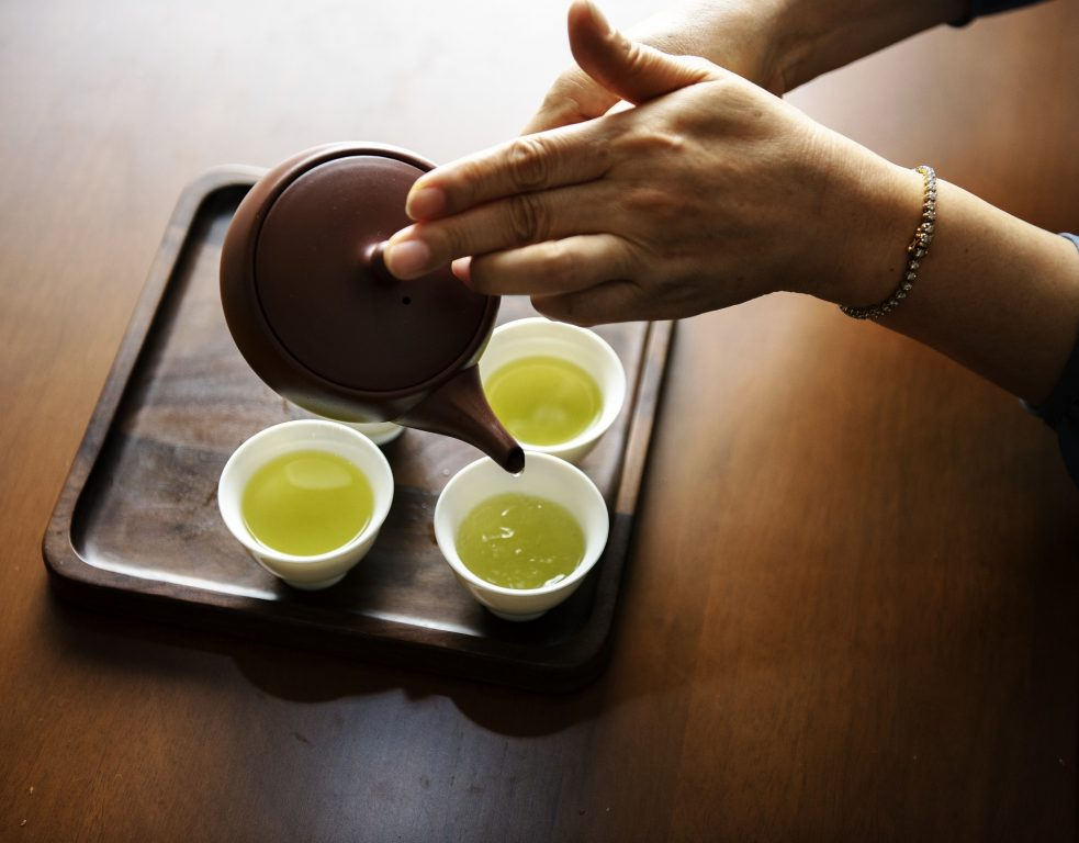 Gingivitis - Image of a woman's hands pouring green tea