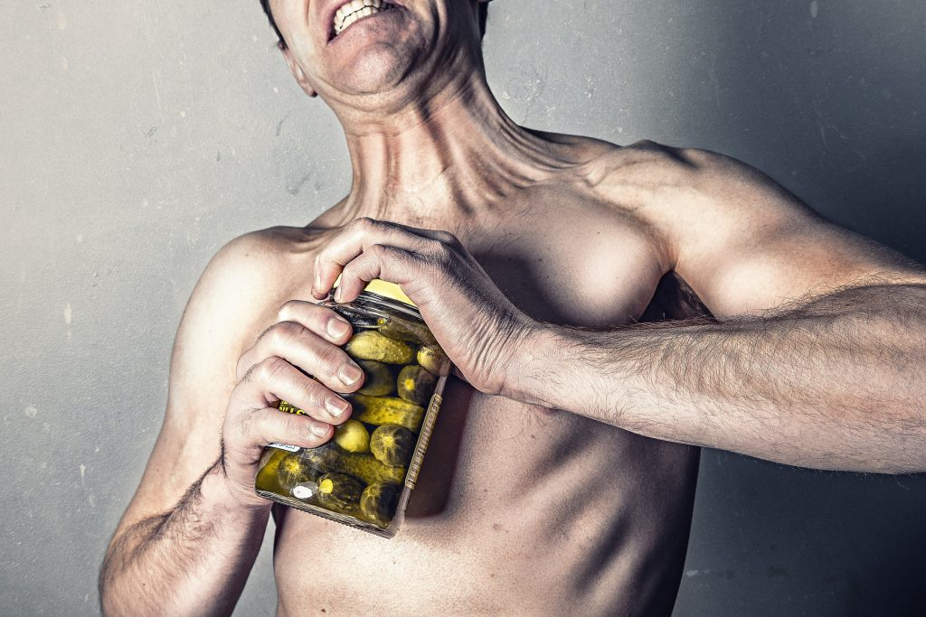 Image of a man straining to open a pickle jar