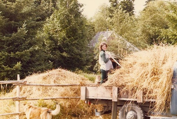 Pregnant woman on truck bailing hay, smiling