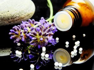 Homeopathy - Image of a bottle, rock, purple flower and little white round pulls on a glass table