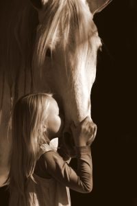 Image of a young blonde girl kissing a white horse
