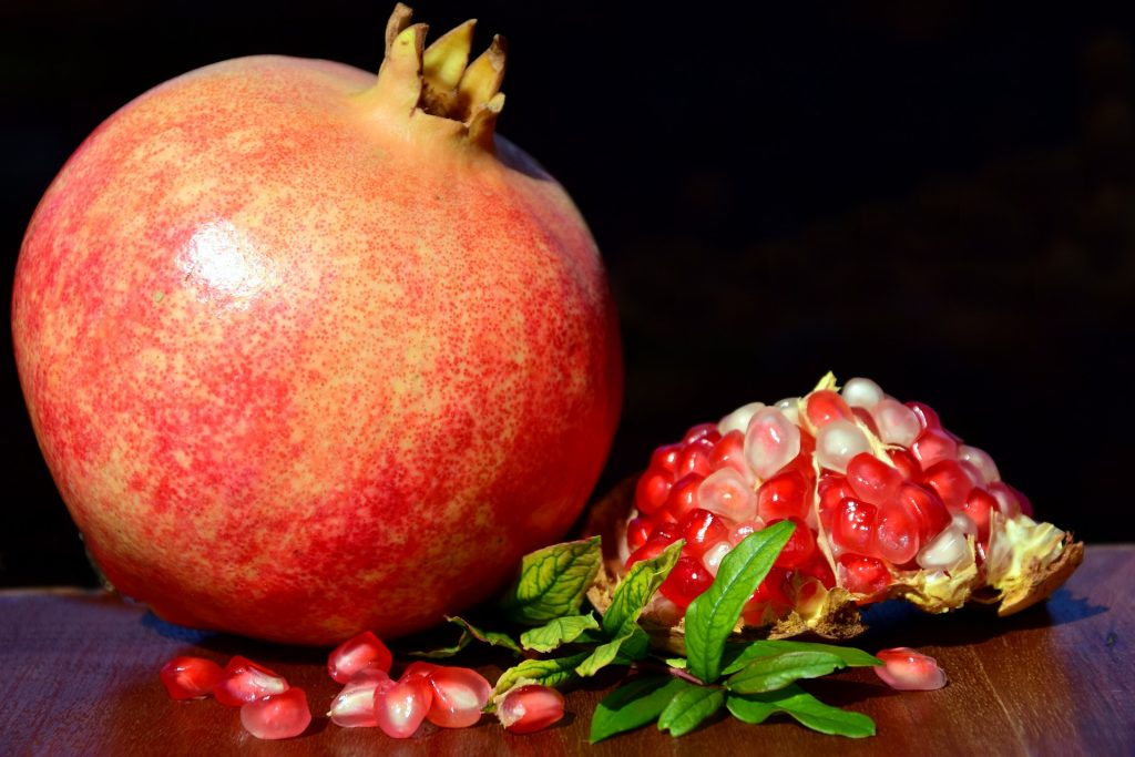 Photo of whole pomegranate and inside of anoth