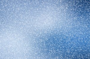 Image of falling snow against blue sky