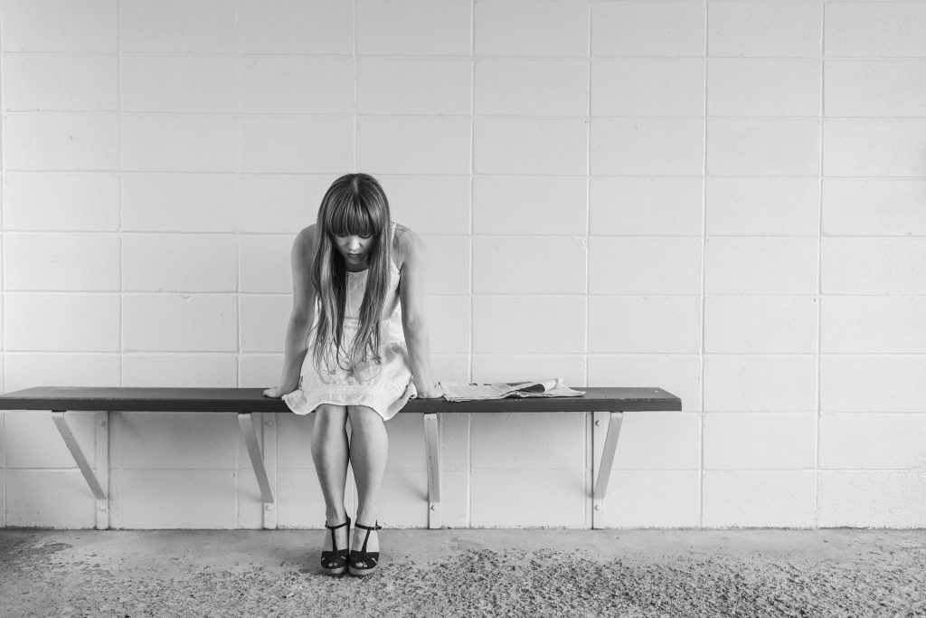 Depression - Image of a girl with head down, sitting on a bench alone