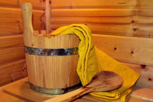 Image of a towel, wooden bucket and ladle in a wooden sauna room