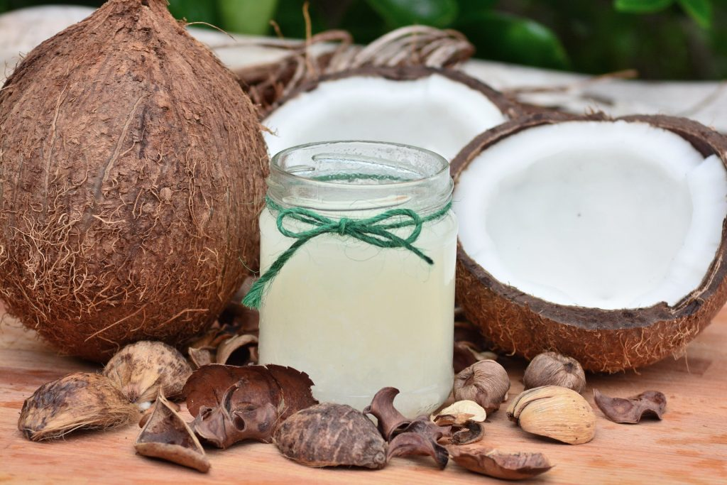 Jar of coconut oil with coconuts on a table