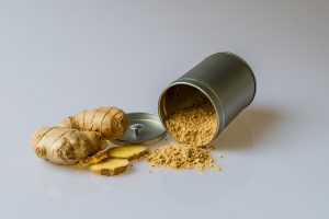 Image of a can of ginger spilling over and fresh slices of ginger