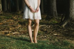 Woman wearing a white sundress walking barefoot
