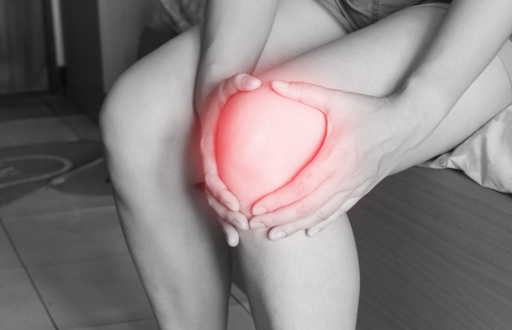 Woman clutching inflamed knee