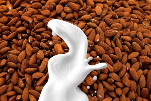 Lactose Intolerance - Image of milk spilling over almonds