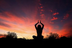 Yoga - Image of a woman in a sitting yoga pose in front of a sunset