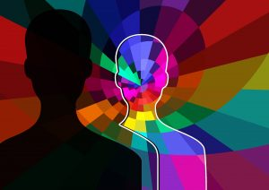 Cognitive Behavioral Therapy - Image of a human silhouette with many colors in and surrounding it. Another black silhouette facing it
