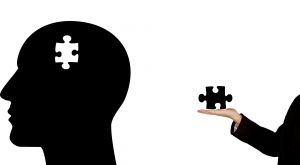 Silhouette of a head with a jigsaw puzzle-shaped piece missing; a hand holding the piece behind the head