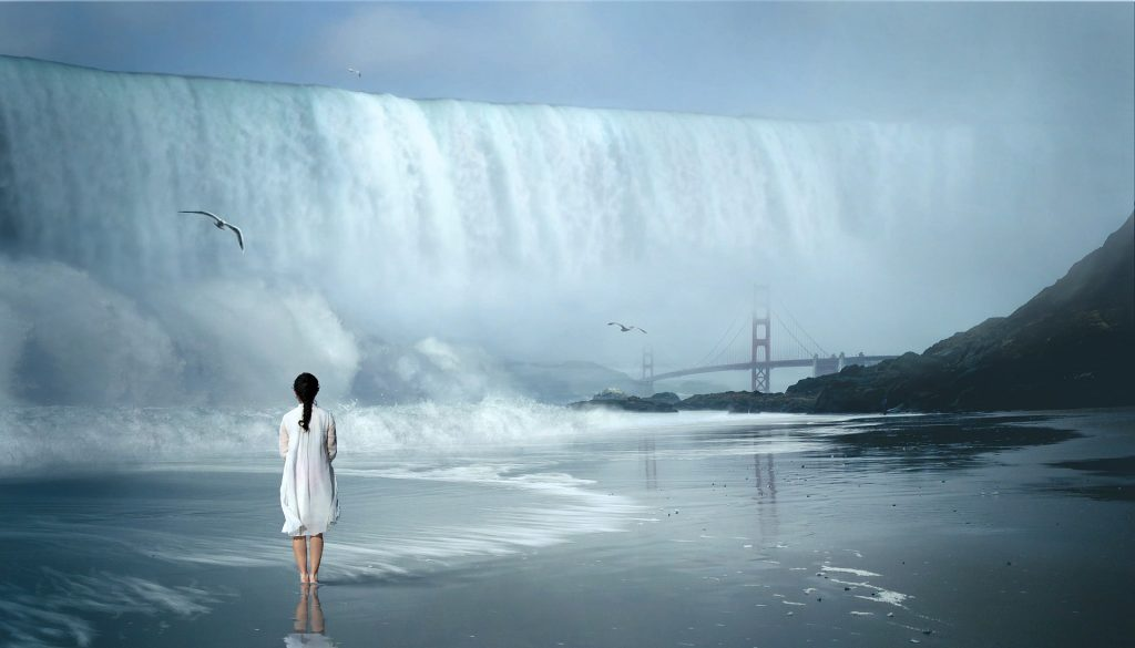 picture of a girl standing on a beach watching a wall of water wash over the golden gate bridge