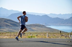 Man running on road, pasture, water, mountains in background