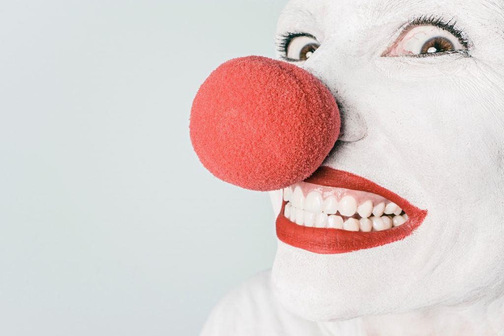 clown with red nose, white face
